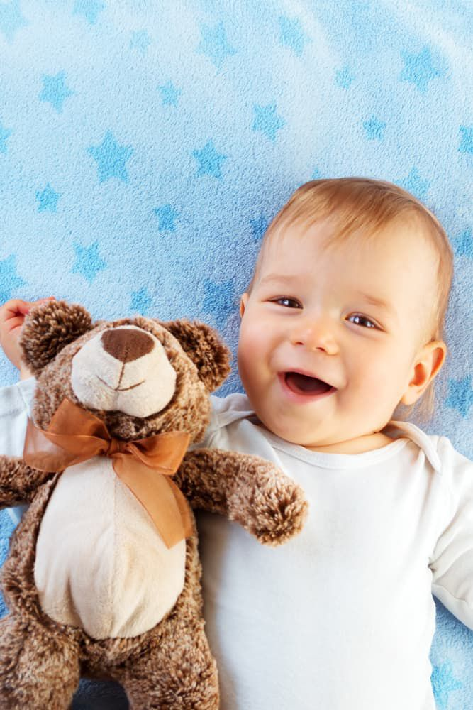 Cute infant with stuffed toy laughing