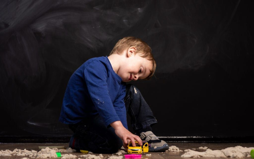 Child playing with toys against black background