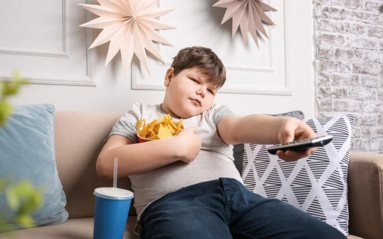 Obese child with snacks and controller on couch