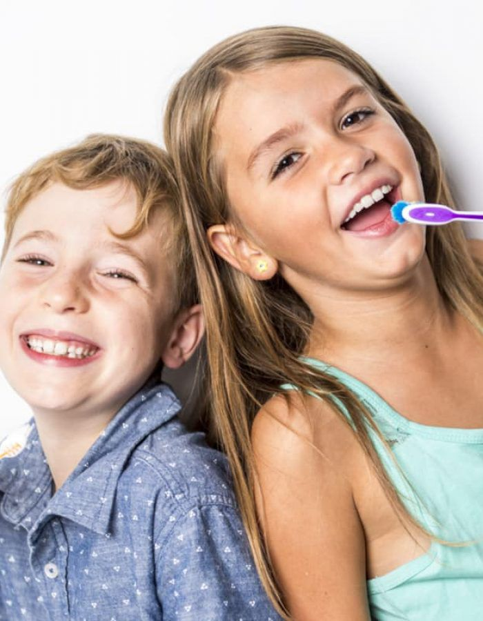 Young children smiling and brushing their teeth