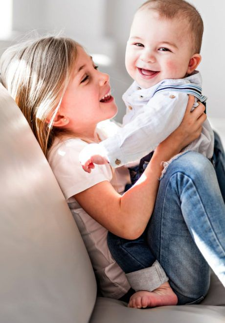 Young girl playing with her newborn brother