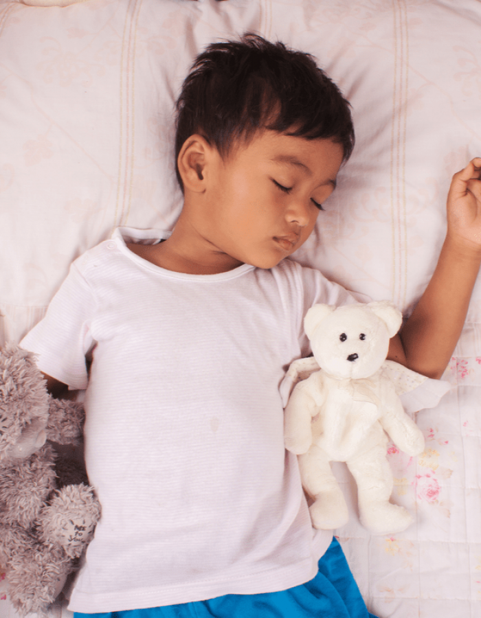 young boy sleeping with his stuffed toys